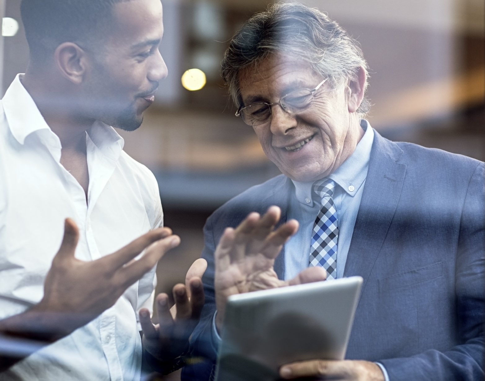 Older business man with young man looking at tablet