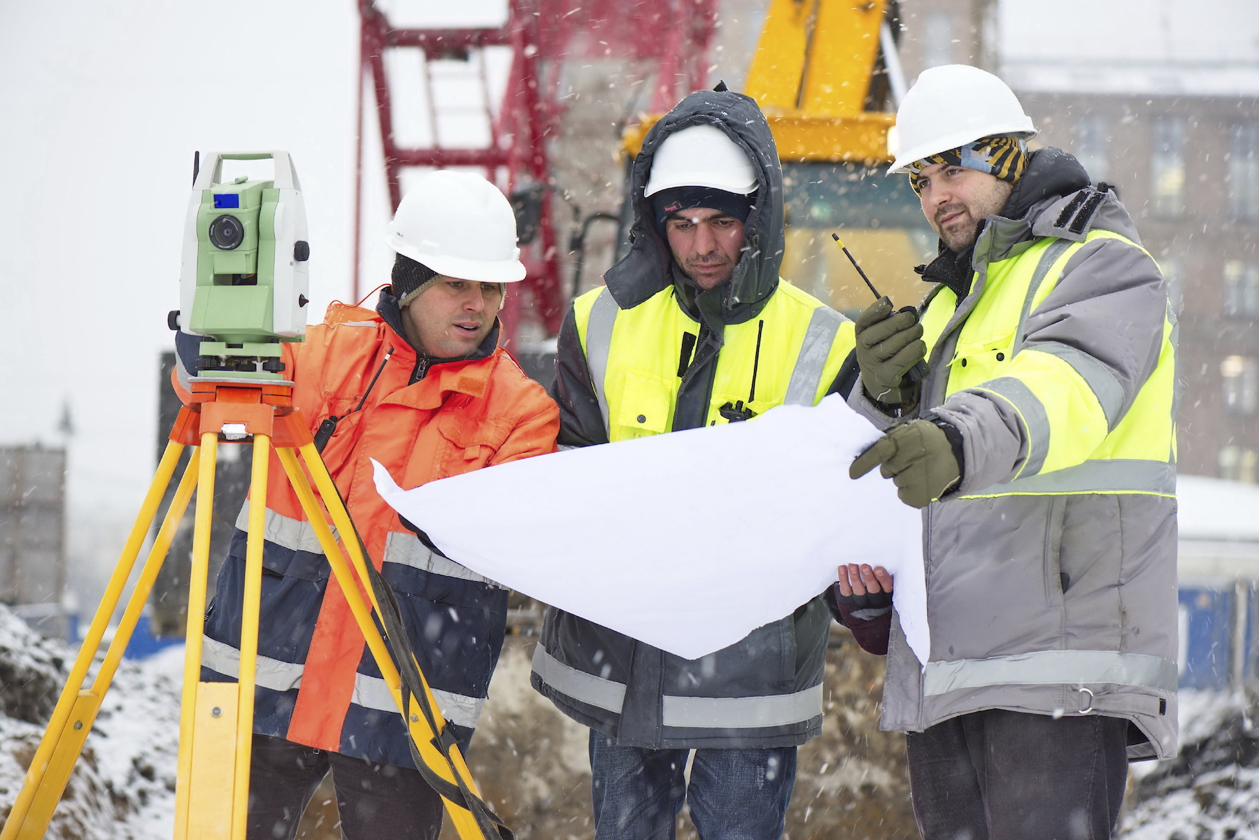 Civil engineers at construction site are inspecting ongoing works according to design drawings in winter conditions